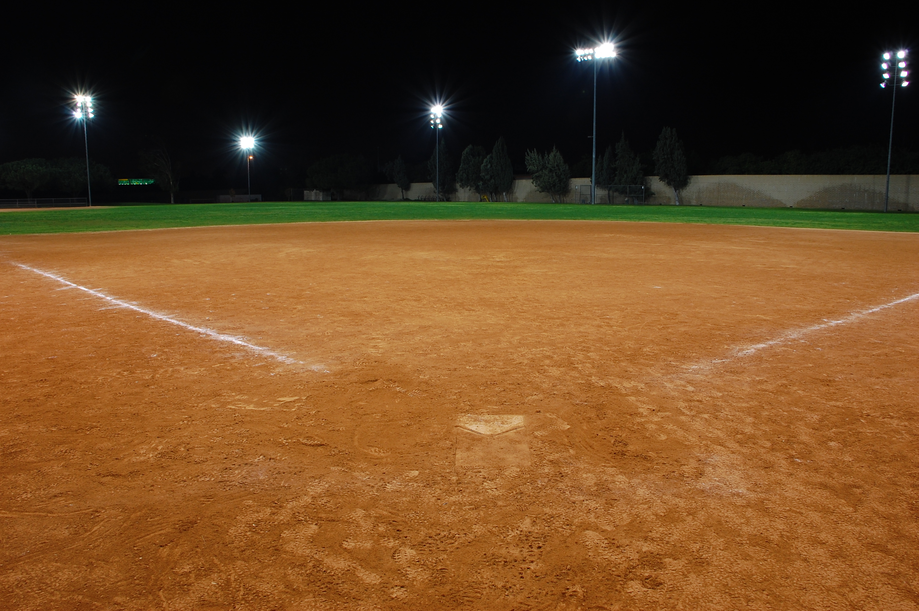 a softball field at night after a game with the lights on.